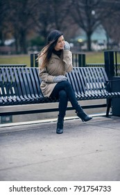 Attractive young woman sitting on urban park bench smiling
