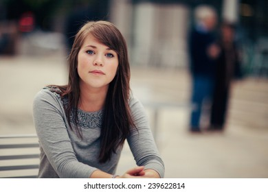 Attractive Young Woman Sitting outside serious