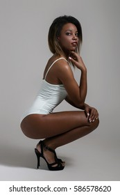 Attractive young woman sitting wearing white lingerie.