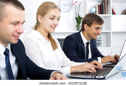 Attractive young woman sitting and working on computer with coworkers in office