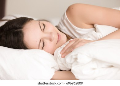 Attractive young woman sleeping comfortably in cozy bed on white soft pillow covering with blanket, enjoying enough sleep with smile on pretty face, see dreams, lucid dreaming, close up head shot