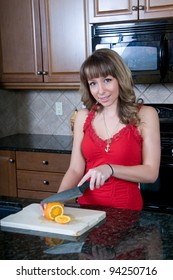 Attractive young woman slices oranges