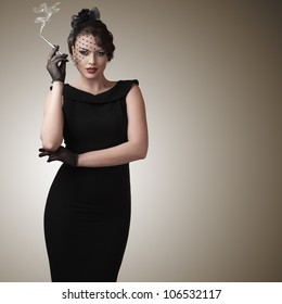 Attractive young woman with slim cigarette retro style portrait