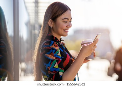 Attractive young woman with smartphone and coffee in the city