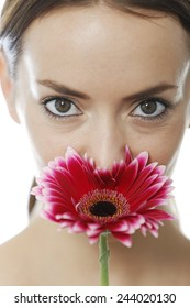 Attractive young woman smelling a red flower
