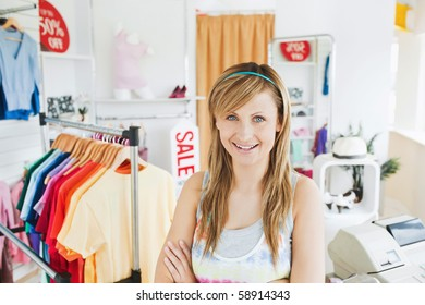 Attractive young woman smiling at the camera standing in a clothes store
