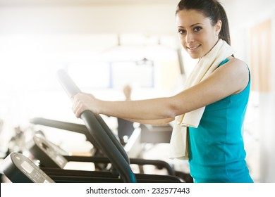 Attractive young woman smiling and doing cardio exercise on treadmill at gym.