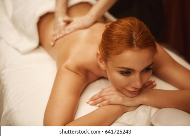 Attractive young woman smiling joyfully while professional masseuse massaging her back at spa center wellness vitality relaxing hotel resort travel therapy recreation rejuvenation luxury living