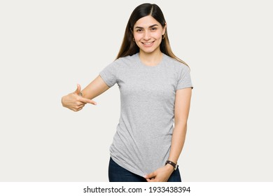 Attractive young woman smiling and pointing to her gray mock up t-shirt. Female t-shirt mock up template for design print
