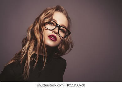 Attractive young woman in spectacles. Studio shot. Beauty, fashion concept. Optics style.