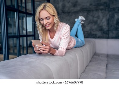 Attractive young woman spending time at home. Lying on sofa with smart phone