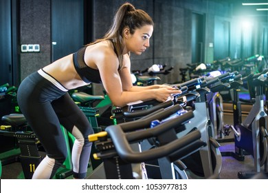 Attractive young woman in sportswear cycling in gym.