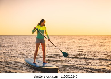 Attractive young woman at stand up paddle board with sunset colors