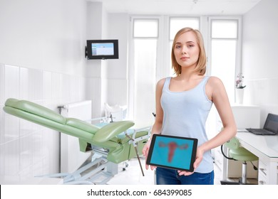 Attractive young woman standing in the gynecological room at the hospital smiling to the camera holding digital tablet with a picture of uterus feminine health gynecology patient medicine copyspace.