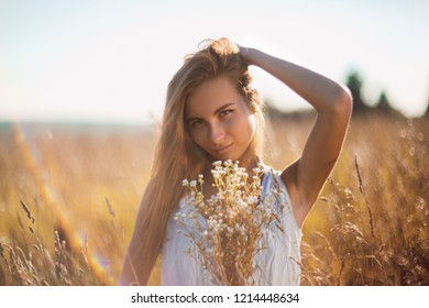 Attractive young woman standing in the meadow in sleeveless jean sundress handing her long hair