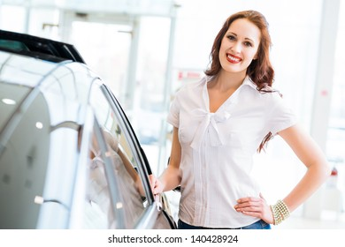 attractive young woman standing near a car in a showroom, chooses a car to buy