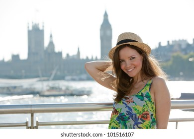 Attractive young woman standing on bridge over the River Thames, London, UK