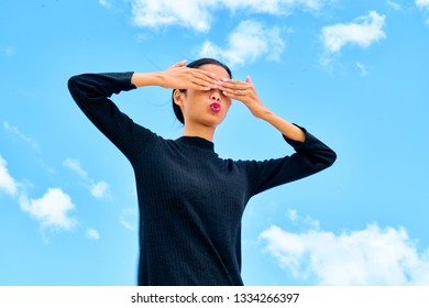 Attractive young woman standing on white sand covering her eyes with her hands with embarassed expression.