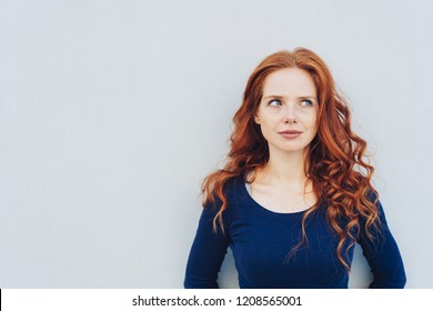 Attractive young woman standing pondering a problem looking up with a contemplative expression against a white exterior wall with copy space