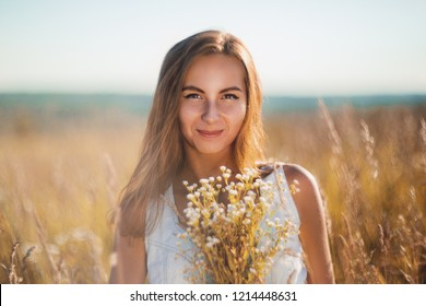 Attractive young woman standing smiling in the meadow in sleeveless jean sundress looking in camera