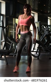 Attractive Young Woman Standing Strong In The Gym And Flexing Muscles - Beautiful Athletic Fitness Model Posing After Exercises