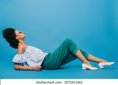 attractive young woman in stylish clothes and sunglasses lying on floor on blue