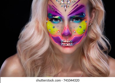 Attractive young woman with sugar skull makeup. Mexican Day of the dead woman wearing sugar skull makeup. Creative colorful and glamor make-up. Halloween concept.
