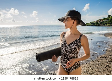 Attractive young woman in swimsuit and hat going to do yoga with black mat in her hand  on tropical beach. Healthy lifestyle concept.