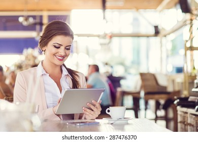 Attractive young woman with tablet in cafe