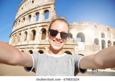Attractive young woman taking selfie in front of Colosseum in Rome