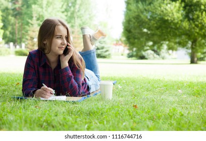 Attractive young woman talking on phone lying on the grass in a summer park