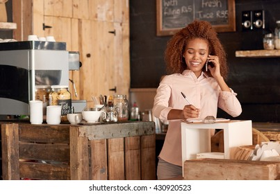 Attractive young woman talking on the phone while working in cafe