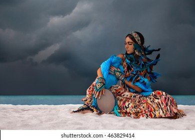attractive young woman with tambourine outdoors. One minute before storm