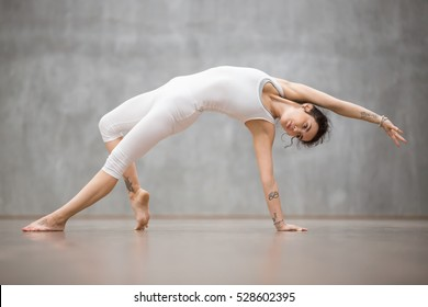 "Attractive young woman with tattoo on her foot meaning ""Wild kitty"" working out against grey wall, doing yoga, pilates exercise. Camatkarasana, Wild Thing or Flip-the-Dog posture. Full length"