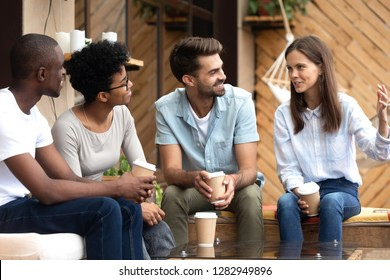 Attractive young woman telling funny story to multi-ethnic different friends, attractive people sitting on summer terrace drinking coffee beverage in carton cups having fun spending weekend together