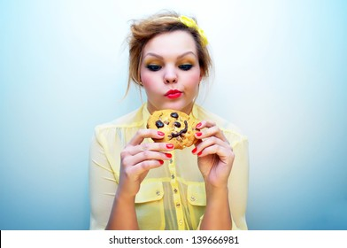 Attractive young woman tempted to eat a chocolate chip cookie
