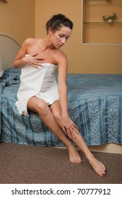 The attractive young woman in towel with cosmetic cream sits on bed at home. Concept of body care.