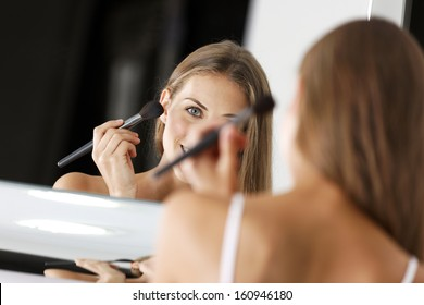 Attractive young woman in underwear applying make up in bathroom.