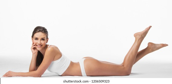 Attractive young woman in underwear is laying and smiling with happiness. Isolated on background