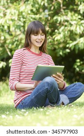 Attractive Young Woman Using Digital Tablet In Park