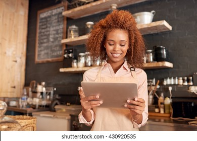 Attractive young woman using a digital tablet while working in a cafe