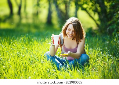 Attractive young woman using her phone and drinking coffee, sitting on meadow.