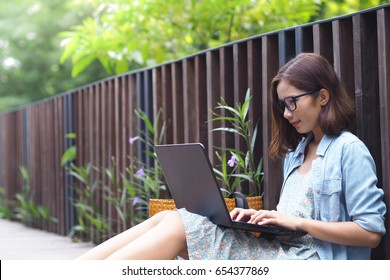 attractive young woman using laptop outside