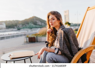 Attractive young woman in vintage jeans sitting on recliner in outdoor restaurant. Lovable brunette girl in tweed coat waiting for order in favorite cafe and enjoying nature views.