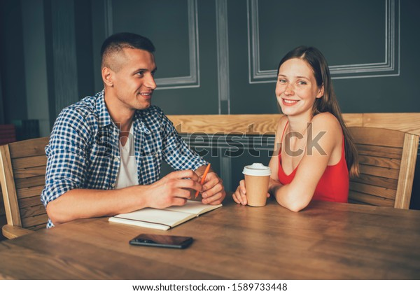 Attractive young woman in vivid red shirt with hot drink to go smiling at camera while sitting at wooden table beside handsome pensive man with pen and notepad in cozy contemporary cafe