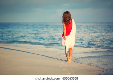 Attractive young woman walking along ocean beach at sunset