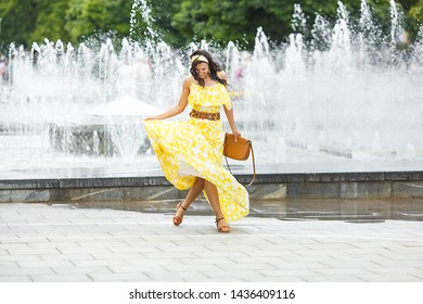 Attractive young woman walking the city. Lady in yellow long dress near the fountain. Beautiful female on summer background.