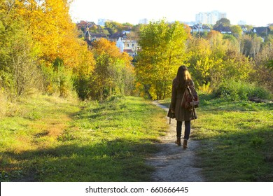 Attractive young woman walking in the forest. Young woman walking over autumn background.Shot of an attractive young woman in the park on an autumn day.