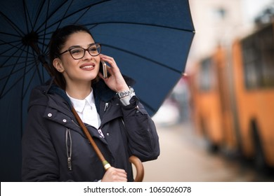 Attractive young woman walking in the street under the rain, holding her cellphone.