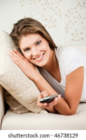 Attractive young woman watching TV